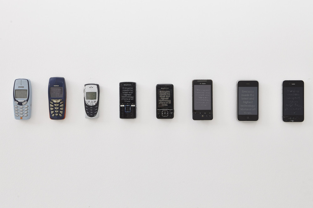 A row of cell phones mounted to the wall. The phones go from older generations on the left to the newest on the right.