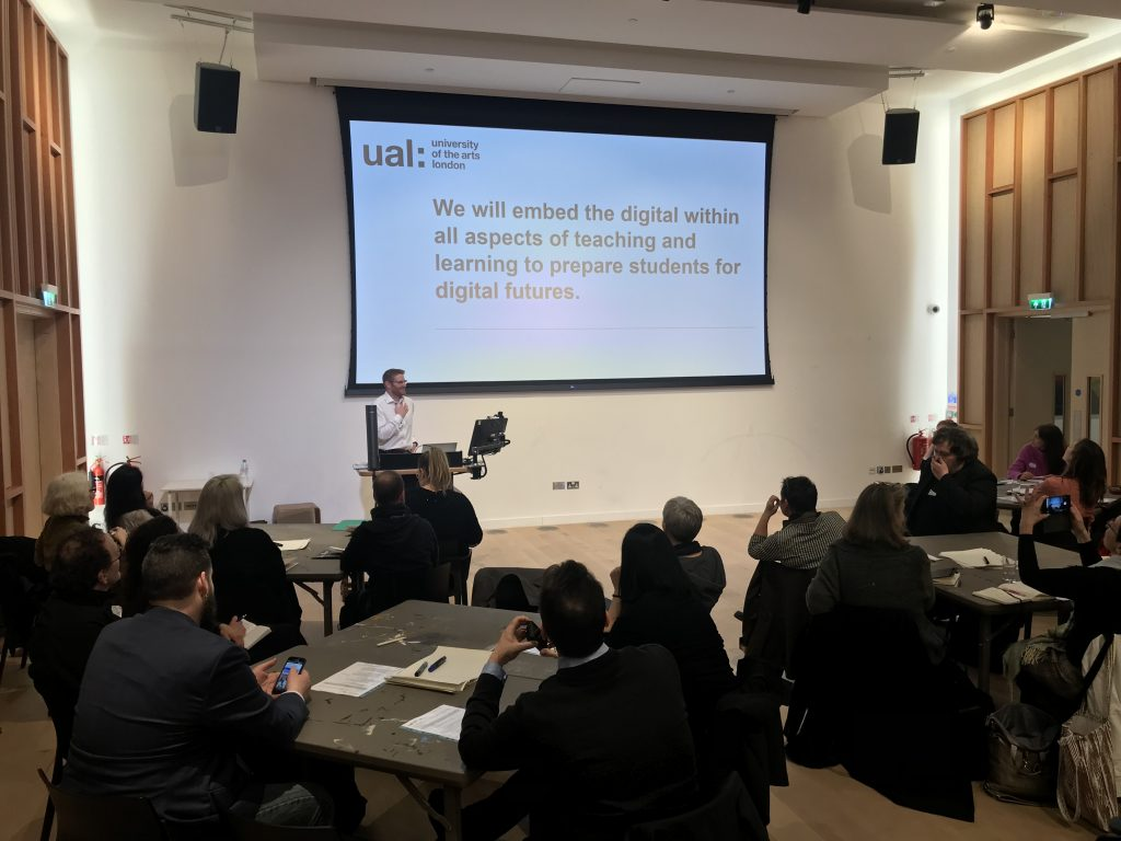 A man is standing at the front of a room behind a podium. There is a projected screen with the note, 'We will embed the digital within all aspects of teaching and learning to prepare students for digital futures.'. There are three tables full of people, many are taking photos of the slide.