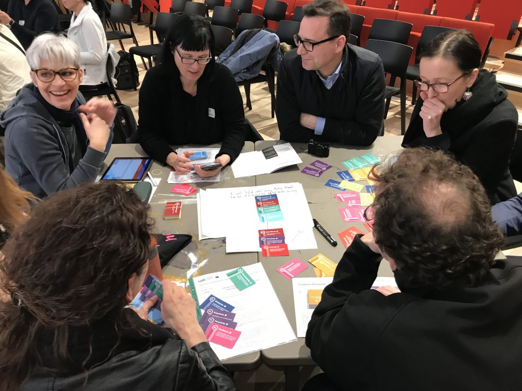 A group of people sitting around a table, all discussing the multi-coloured DCAF cards.