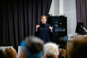 Woman standing to give talk
