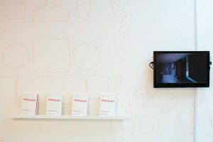 Parallax booklets and TV displayed on a wall