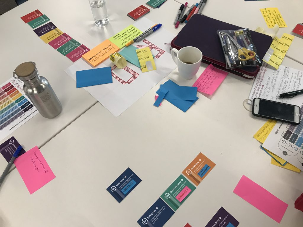 An image of the tables during the DCAF workshop. There are cards spread across the tables with post-its, pens, water bottles, a tea mug, a mobile phone and other items showing a cluttered but productive workspace.