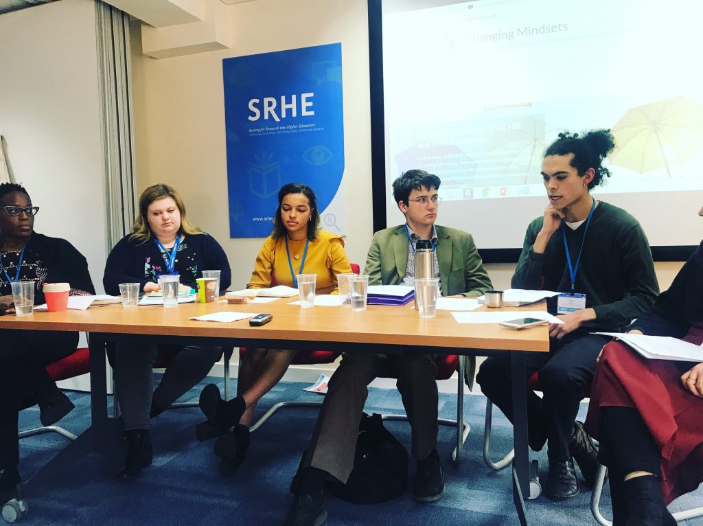 Five students sitting in a row on panel at the SRHE event