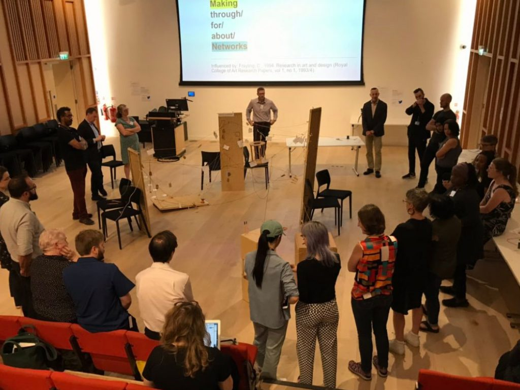 About 30 people standing in a lecture theatre in a circle, discussing a collaborative sculpture made of wood, string and post it notes.