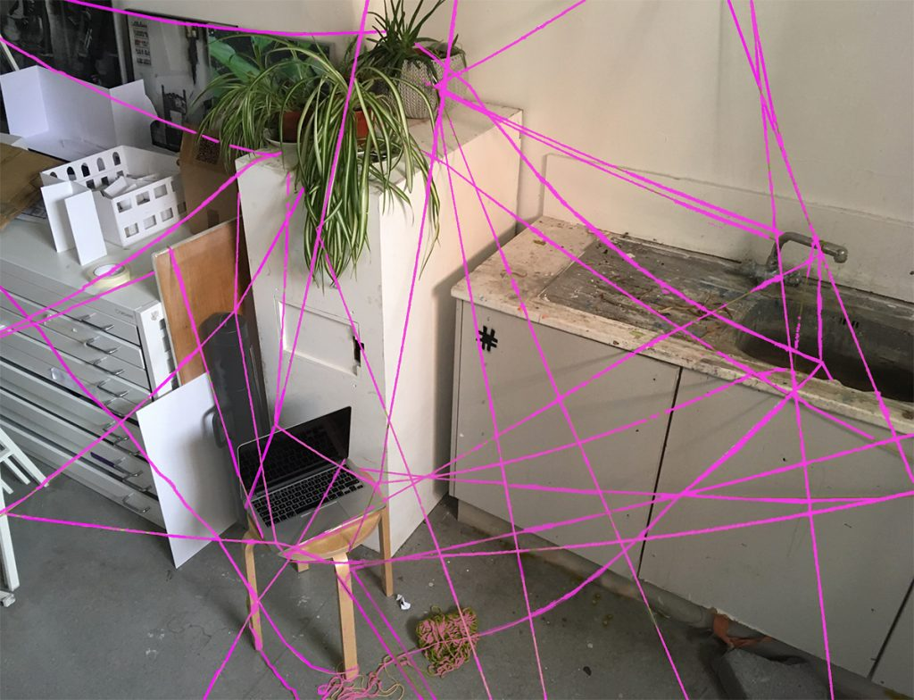 Laptop on a stool in an art studio surrounded by a spiders web of pink wool