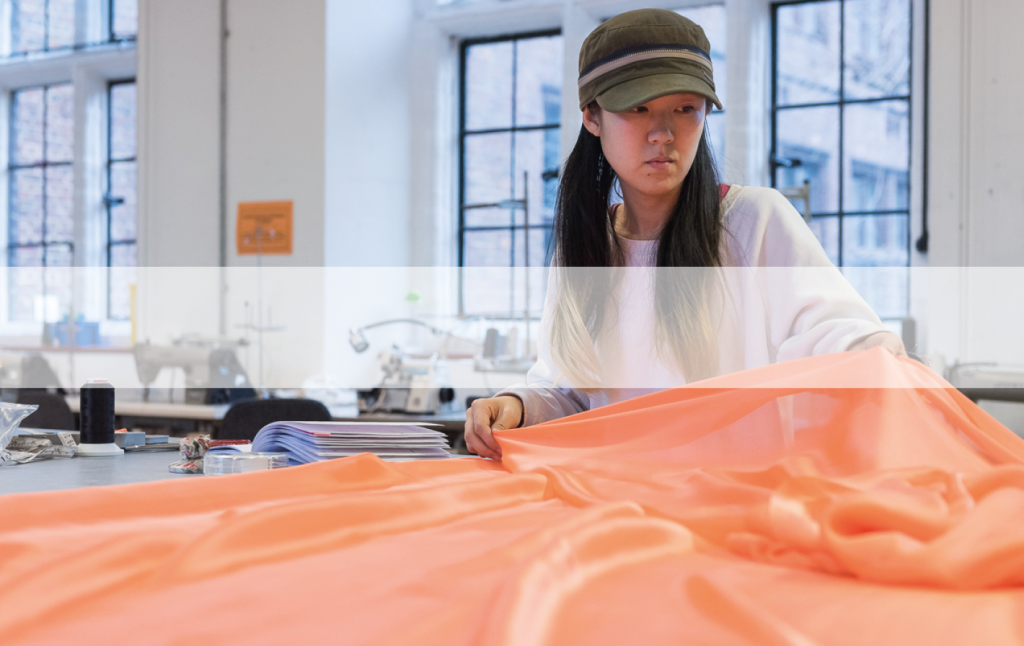 female asian fashion student in studio with working with large piece of orange silk fabric