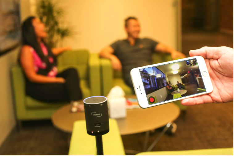 A hand navigating the Mevo app on an iPhone. There are two people sitting in chairs being livestreamed through the camera and app.