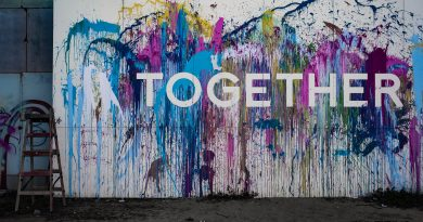 A wall with the word Together painted on it surrounded by multicolour paint splatters.
