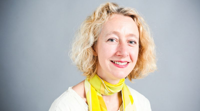 Headshot of Frania wearing a yellow scarf