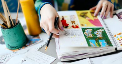 Hand holding a pen while leafing though brightly painted illustrations in sketchbook