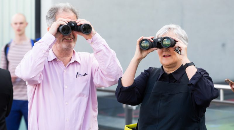 Middle aged man and woman standing on rooftop holding binoculars to their eyes and looking across and past each other