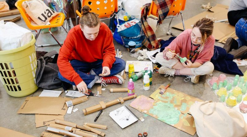 Looking down on 2 students sitting cross legged on a concrete floor, surrounded by cardbard, glue and scissors as they make work.