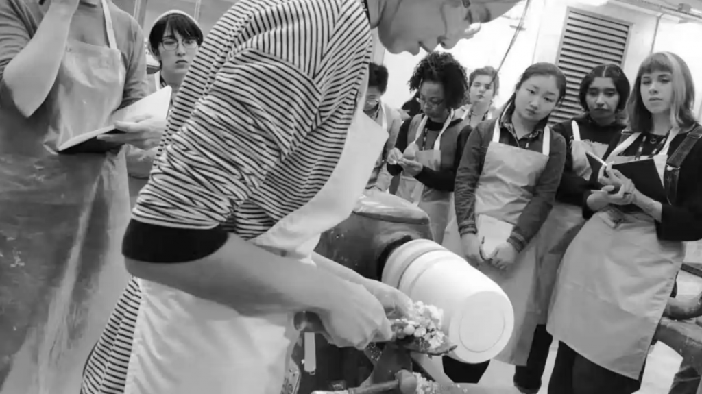 black and white photo taken at a 45 degree angle, showing  a person the foreground making a ceramic pot. In the background students are watching.