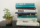 A black table with a succulent plant in a pt on the left and a pile of books on the right. The books are a mix of turquoise, black and white spines.