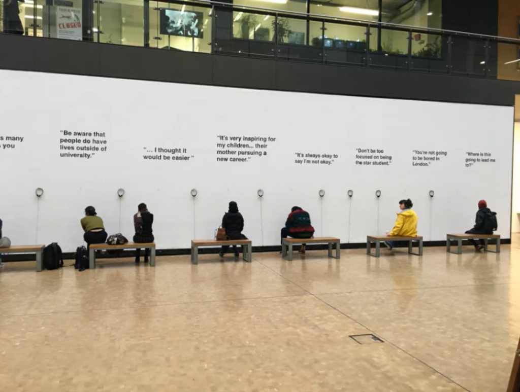 People sitting on benches by a large white wall at CSM, listening to various headsets attached to the wall.